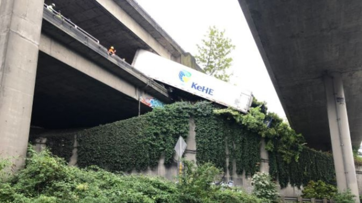 Semi hangs over barrier from I-5 express lanes