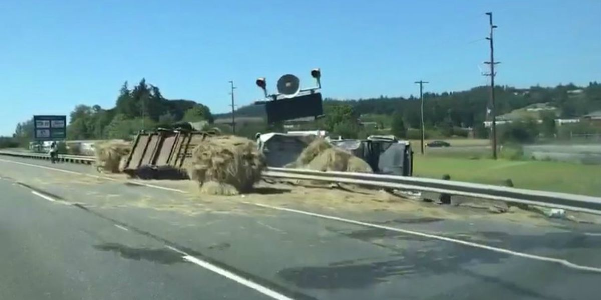Truck carrying hay flips over guardrail on I-5; 1 injured